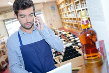 Man In Liquor Store Using Laptop And Talking On Telephone