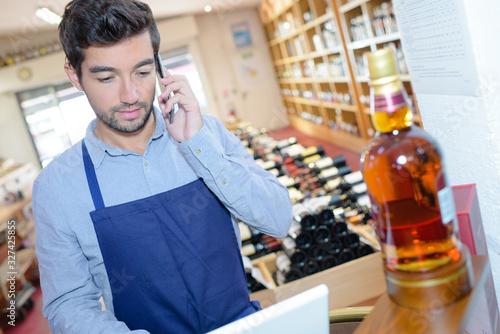 Cuadros en Lienzo man in liquor store using laptop and talking on telephone