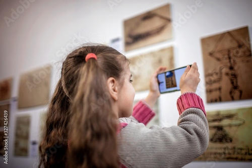 Photo Curious girl exploring a contemporary art exhibition with augmented reality mobi