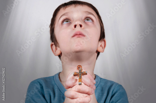 Fotografija Little boy praying and holding rosary