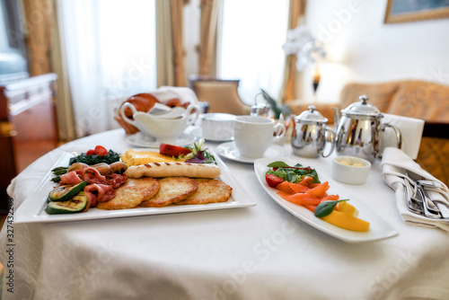 Obraz Luxurious Room Service. Close up of breakfast in luxury hotel room delivered by waiter. Hospitality and vacation concept - fototapety do salonu