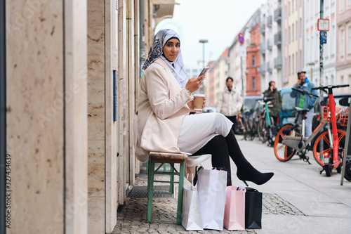 Canvastavla Young beautiful Arabic woman in hijab using smartphone while resting on bench wi