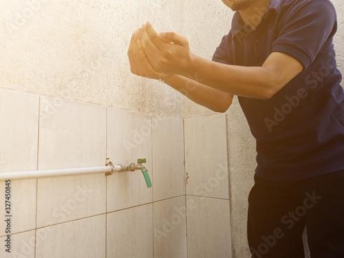 Fotografija A moslem man take ablution before praying