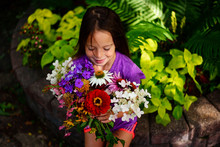 A Young Girl Outdoors With A Bouquet Of Flowers