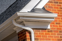 Closeup View Of White Gutter System With Soffit Vent, Gutter Guard, Drop Outlet, Downspout, Vinyl Elbows, Decorative Trim Molding, On The Corner Of A Brick Luxury House In America