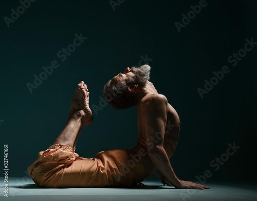 Photo Old man with grey beard doing yoga, pilates, fitness training, stretching exerci