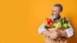 Leinwandbild Motiv Cool old mature senior man with gray beard shopping hold grocery shopping bag with healthy organic vegetables on yellow
