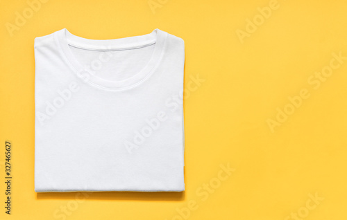 top view of folded white color t-shirt on yellow background, copy space, flat la Fototapet