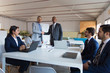 Two businessmen shaking hands in office. Smiling colleagues standing and looking at camera. Business meeting concept