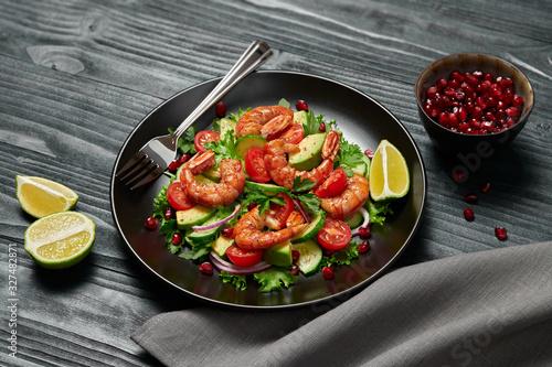 Fototapeta Shrimps salad, avocado, lettuce, cherry tomatoes. Home made vegetarian shrimp salad. Seafood concept. Tasty veg mixed leaves, grilled prawn shrimps in plate on black wood background. obraz