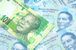 canvas print picture - A close up image of a green ten rand bank note from South Africa in macro on a bed of Mexican twenty peso bank notes