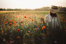 Stylish Woman In Rustic  Dress And Hat Walking In Summer Meadow Among Poppy And Wildflowers In Sunset Light. Atmospheric Authentic Moment.Copy Space. Girl In Countryside. Rural Slow Life.