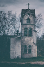 The Tower Of An Old Abandoned Church Against A Cloudy Stormy Sky. Beautiful Background For Greeting Card Or Wallpaper On Halloween