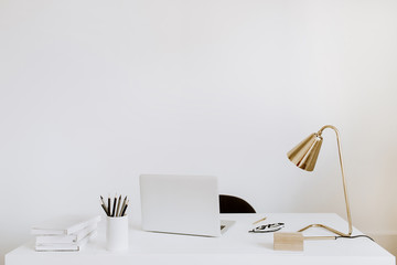 Office with laptop, lamp, notebooks. White working study cabinet. Outsourcing freelancer, blogger, boss workspace.