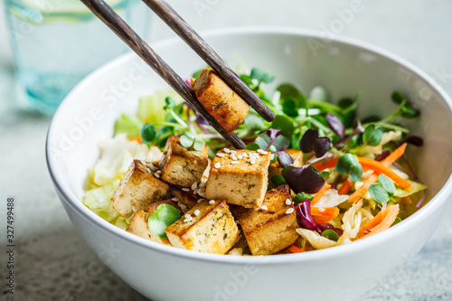 Photo Fried tofu salad with seedlights and sesame seeds in white bowl
