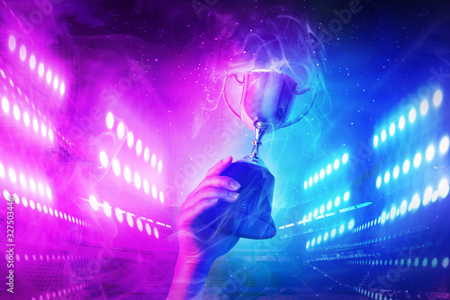 Trophy with smoke effect holding on hand and background blue and violet light for e-sport winner event Tableau sur Toile
