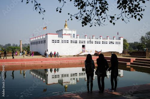 Templo de Lumbini reflejado en el agua con personas alrededor Canvas Print