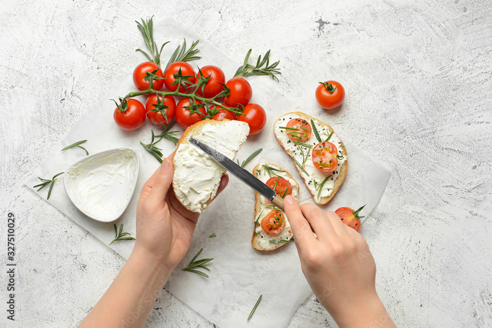 Fototapeta Woman making tasty sandwich with cream cheese on white background