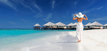 Woman Wearing White Dress And Hat Walking Towards Overwater Bungalows