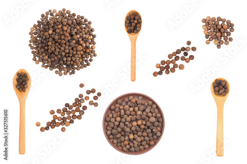 Photo Set of spice allspice isolated on white background in clay plate, wooden spoon,