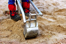 A Child Shovels Sand With A To...