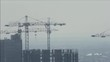Tower cranes and builders working on construction of the building