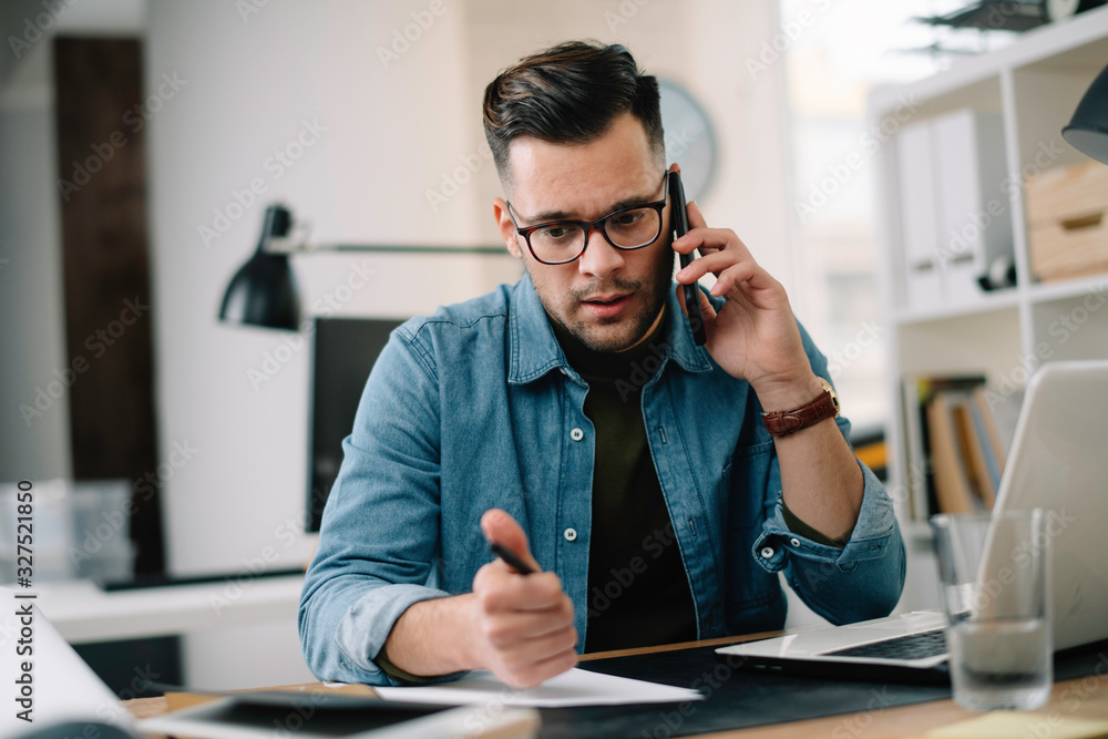 Fototapeta Businessman in office. Handsome man talking on phone at work.