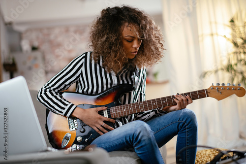 Fototapeta African woman with guitar. Beautiful woman playing guitar.  obraz