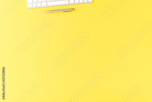 Fototapety, obrazy: Elegant office desktop with computer keyboard and pen on yellow table. Business background. Top view