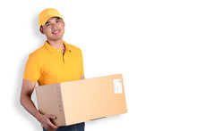 Happy Delivery Man In Yellow Polo Shirt Uniform Holding Parcel Post Box Isolated Over White Background. Smiling Courier Delivery Man.