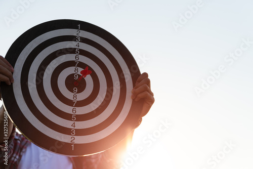 Man hand holding a target with darts hitting the center Wallpaper Mural