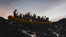 Boat With Refugees Floating In The Sea