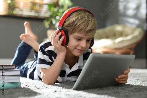 Obraz Cute little boy with headphones and tablet listening to audiobook at home - fototapety do salonu