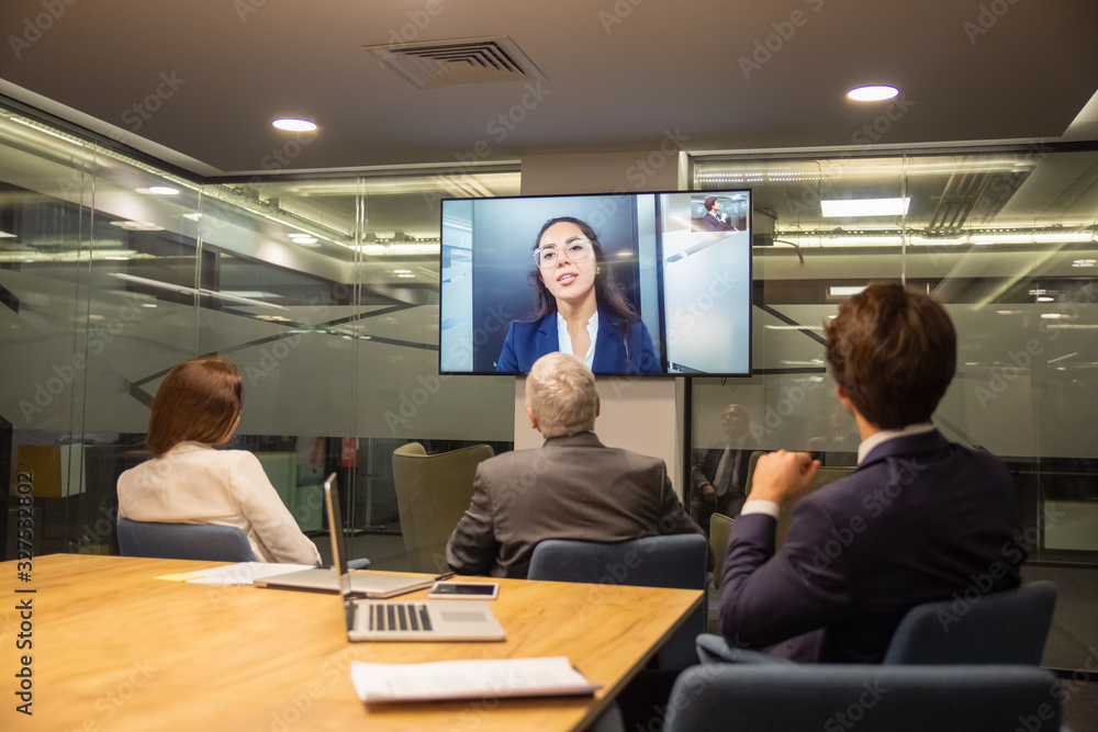 Fototapeta Back view of employees listening to speaker during conference. Business people looking at monitor screen during video conference in office. Business conference concept
