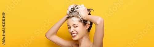 panoramic shot of happy girl with closed eyes washing hair on yellow background