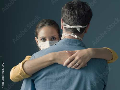 Millennials couple wearing a protective mask and hugging Tableau sur Toile