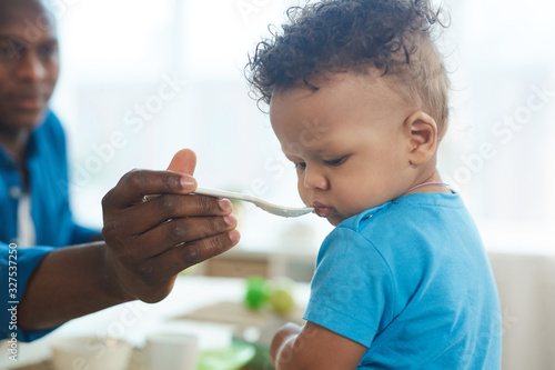 Fototapeta Side view portrait of cute African-American toddler refusing to eat food from sp