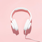 Flat lay white headphones on modern pale pink table wallpaper. Free space for creative design text and content.
