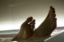 Feet In The Bathroom Closeup. Steamed Female Heels. Manicure.