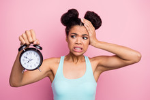 Photo Of Funny Dark Skin Lady Hold Metal Classic Alarm Clock Hand On Head Grimacing Oversleep Missed Work Afraid To Be Late Wear Blue Tank-top Isolated Bright Pink Background
