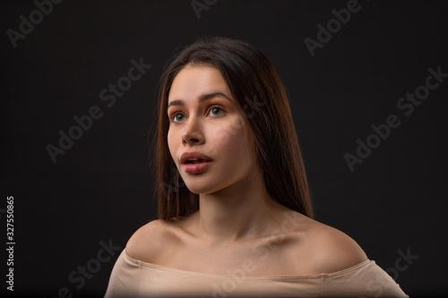 Sarcasm emotion Brunette girl portrait against black background Wallpaper Mural