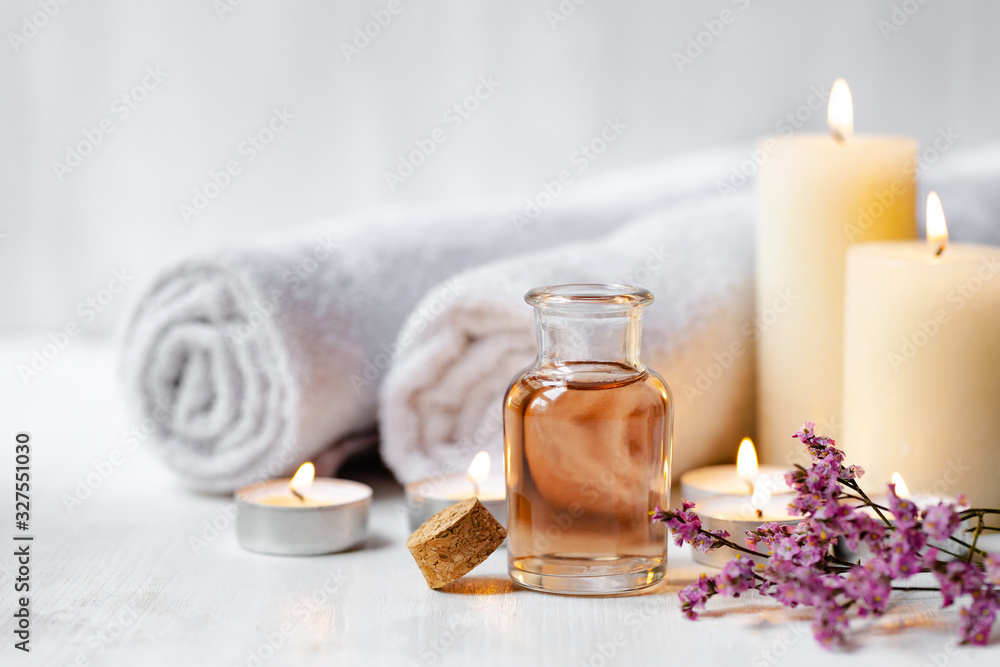 Fototapeta Concept of spa treatment in salon. Natural organic oil, towel, candles as decor. Atmosphere of relax, serenity and pleasure. Anti-stress and detox procedure. Luxury lifestyle. White wooden background