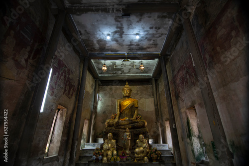 Ancient golden buddha statue in church, ancient temple is Wat Bang Kung, outside is covered with root of banyan tree Canvas Print