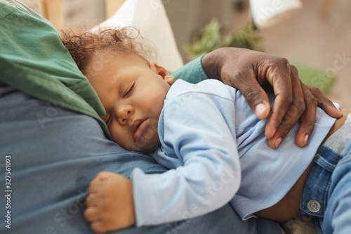 Valokuvatapetti High angle view at cute mixed-race baby sleeping in fathers arms