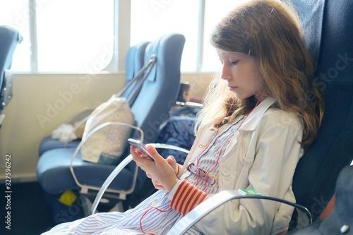 Carta da parati Girl child using smartphone while sitting inside ferry