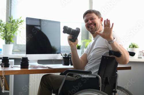 Stampa su Tela Male photographer sitting on wheelchair at table