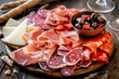 Cures meat platter with cheese and spicy olives served as traditional Spanish tapas on a wooden board. Selection of ham, salami and goat cheese
