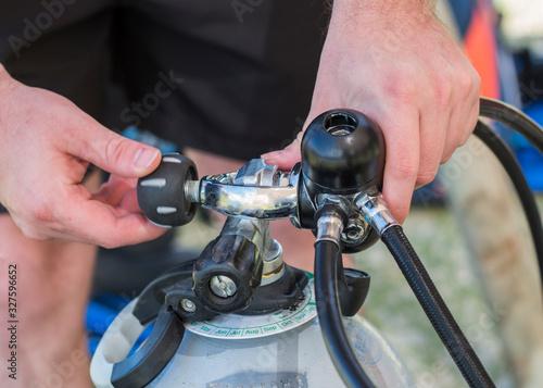 Scuba diving equipment close up of a man attaching an A-clamp regulator to a cylinder Canvas Print