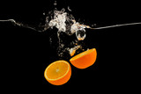 Falling citrus fruits. Orange halves splattering into water on black background
