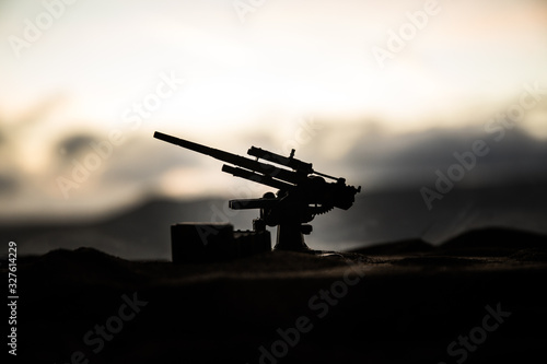 An anti-aircraft cannon and Military silhouettes fighting scene on war fog sky background, World War Soldiers Silhouettes Below Cloudy Skyline at sunset Canvas Print